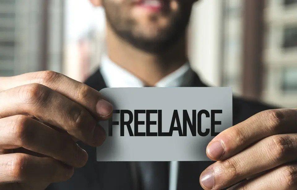 """Homme tenant un papier sur lequel est écrit """"freelance"""""""